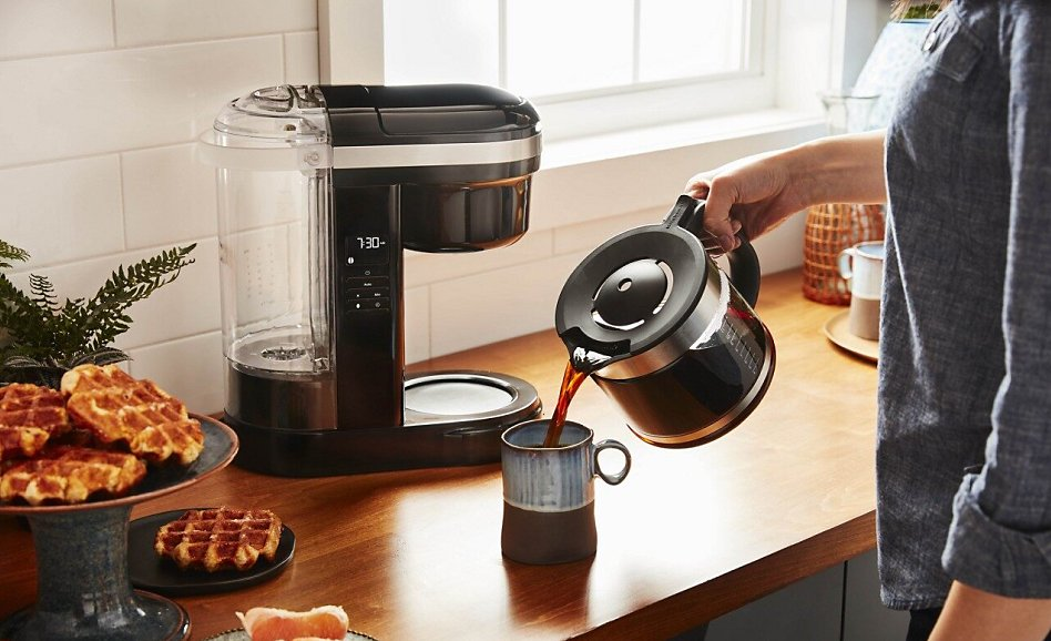 Woman pouring coffee into a mug with drip coffee maker in background