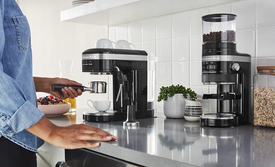 Woman making espresso in bright kitchen