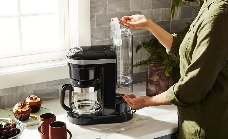 Woman replacing water tank in espresso machine