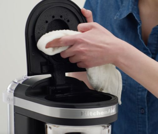 Hand cleaning drip coffee maker shower head with a cloth