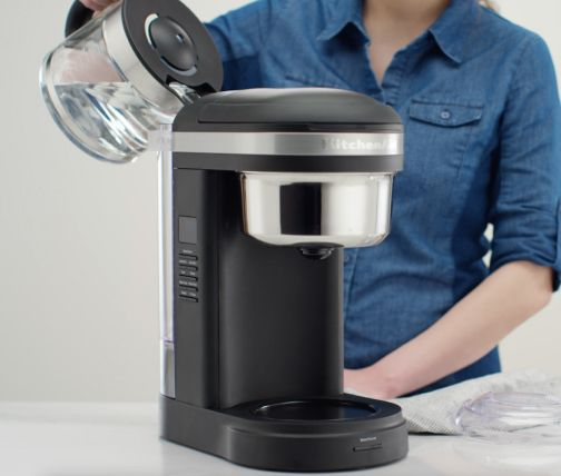 Woman pouring water into coffee machine to rinse after descaling