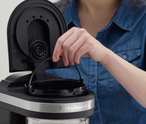 Woman replacing water filter in coffee maker