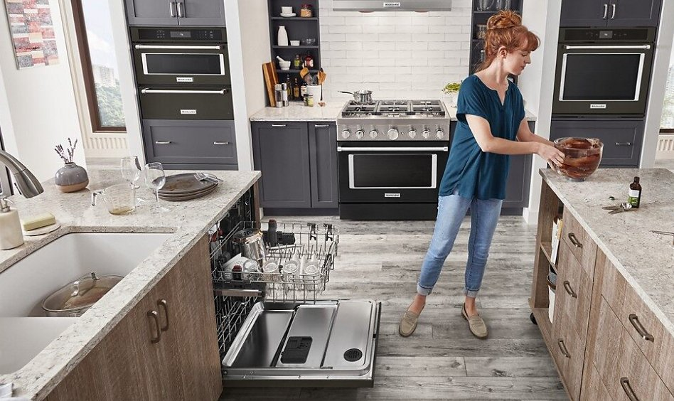 Woman picking up dirty bowl to load into dishwasher