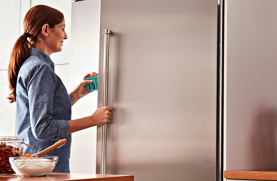 Woman putting items into refrigerator