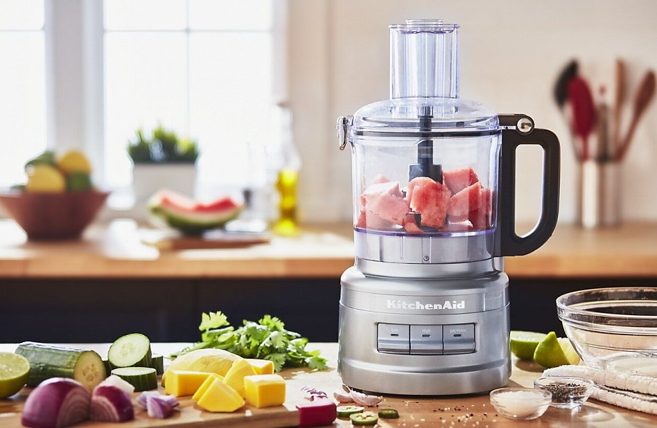 Watermelon in a food processor on counter surrounded by ingredients