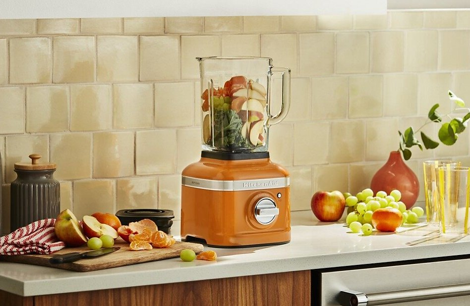 Fruits and veggies in a Honey orange KitchenAid® Blender for baby food