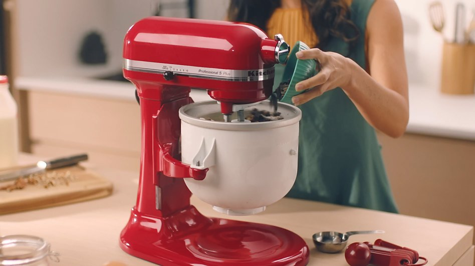 Woman pouring chocolate chips into the bowl of the stand mixer Ice Cream Maker attachment