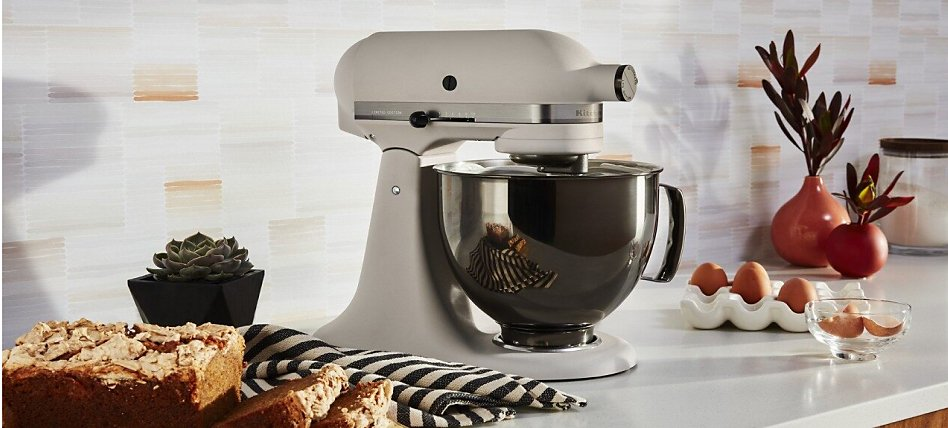 A white KitchenAid® stand mixer beside sliced loaf cake and eggs