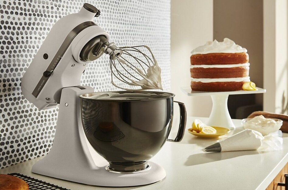 A KitchenAid® stand mixer with whisk attachment and a vanilla frosted cake