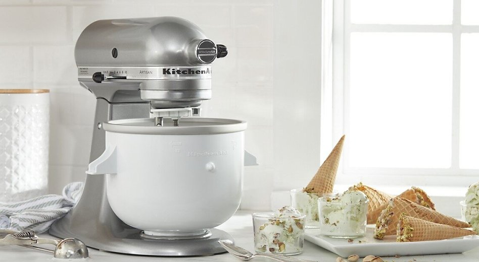 A KitchenAid® stand mixer with Ice Cream Maker attachment beside a tray of ice cream cones