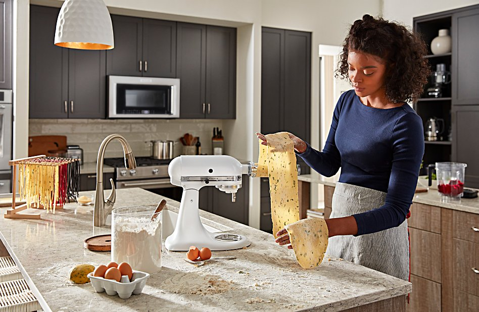 A woman rolling out pasta sheets with a white KitchenAid® stand mixer
