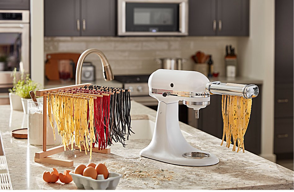 Three different colors of homemade spaghetti noodles drying beside a stand mixer