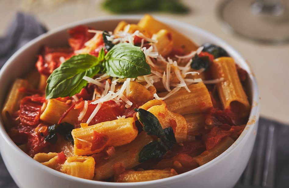 A bowl of rigatoni pasta with fresh tomato sauce, basil and cheese