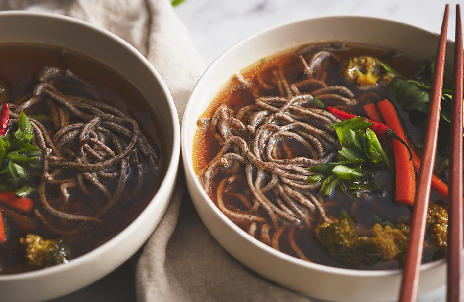 A bowl of buckwheat noodles in an Asian beef broth