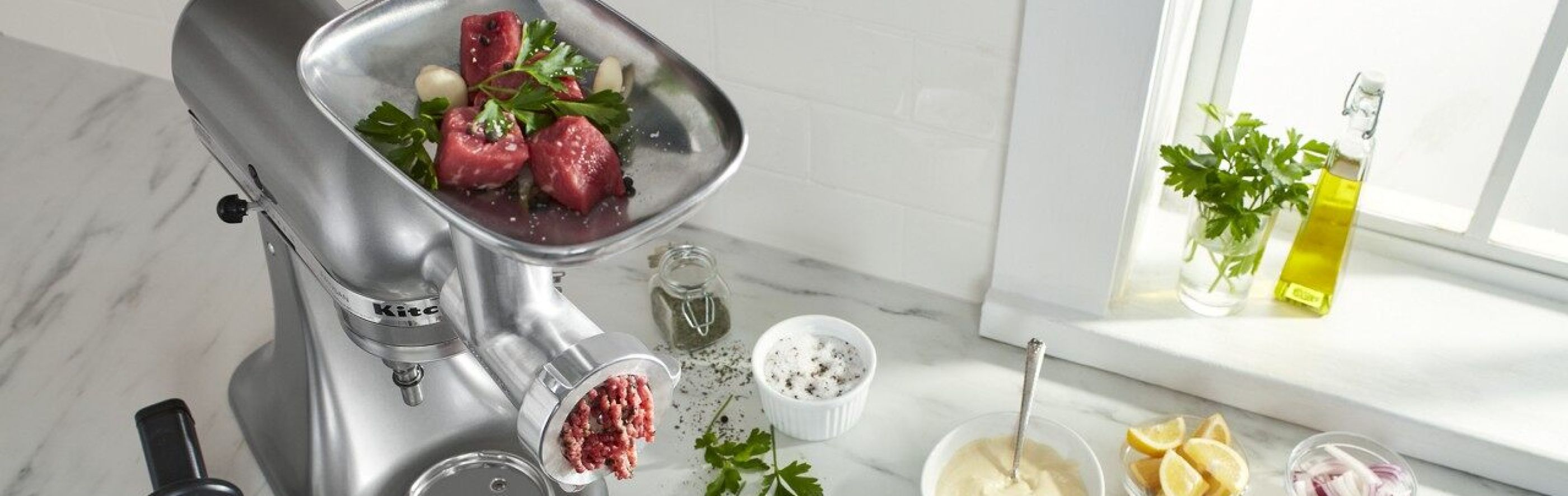 KitchenAid® Stand Mixer with food grinder attachment grinding meat on counter with ingredients