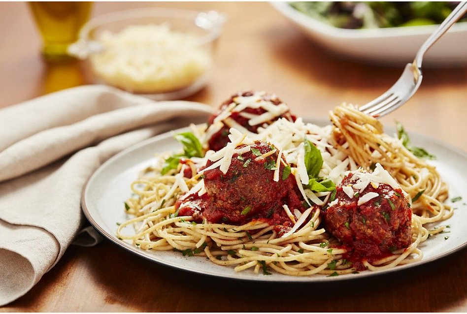 Plate of spaghetti and meatballs with fork twirling noodles