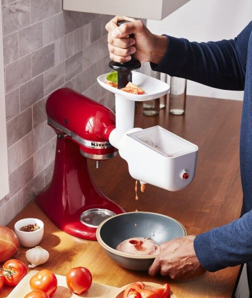 Man grinding and straining tomatoes using a KitchenAid® stand mixer attachment
