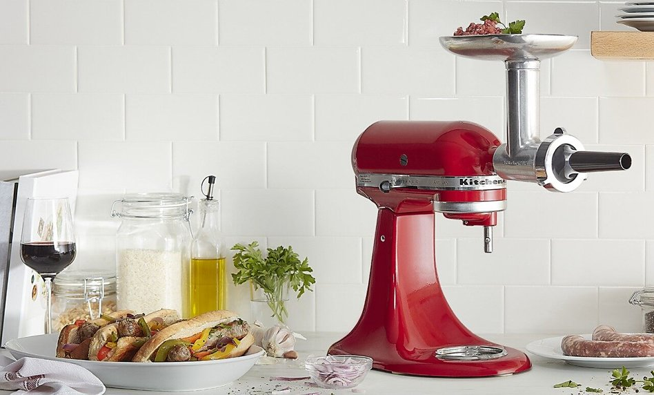 Red stand mixer with sausage stuffer attachment next to prepared bratwurst and glass of wine