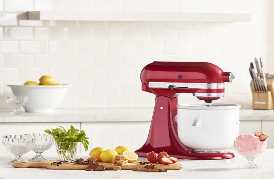 Red stand mixer with Ice Cream Maker attachment surrounded by ingredients and strawberry ice cream