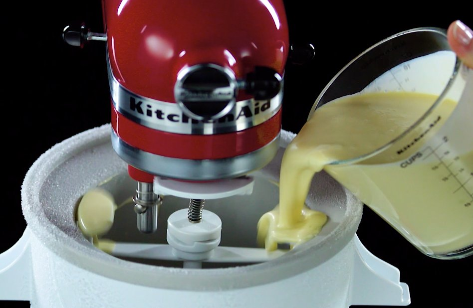 Hand pouring homemade ice cream base into Ice Cream Maker attachment