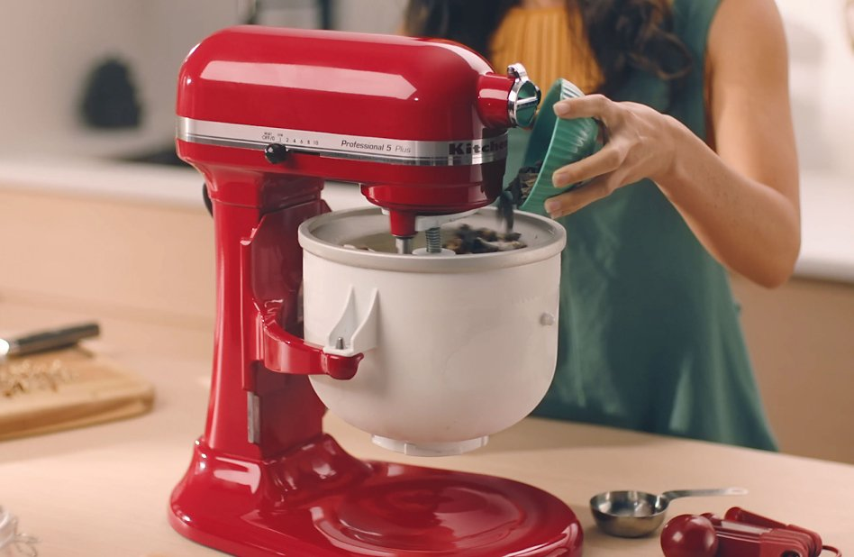 Woman pouring chocolate chips into KitchenAid® Ice Cream Maker bowl