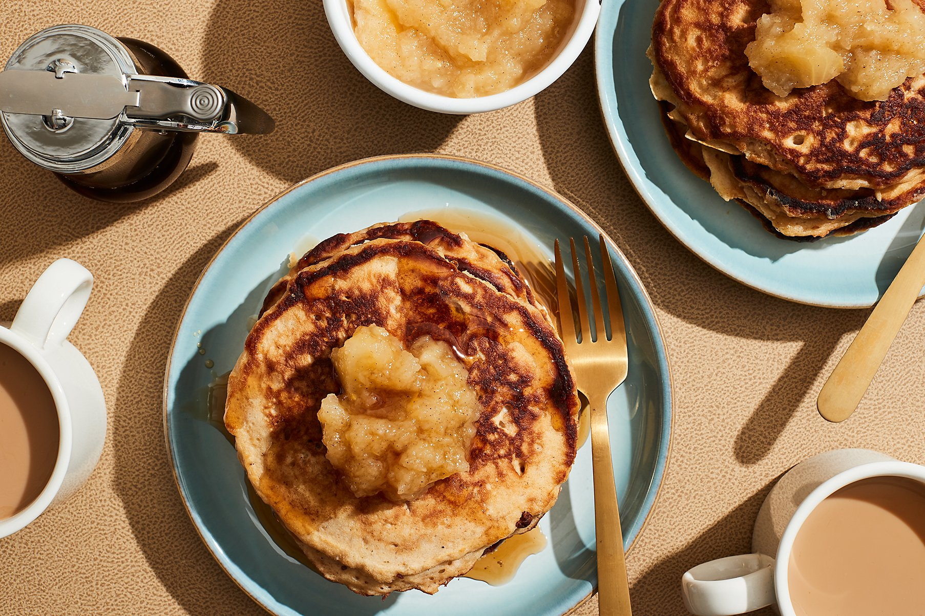 Small stack of applesauce pancakes on a round, light blue plate