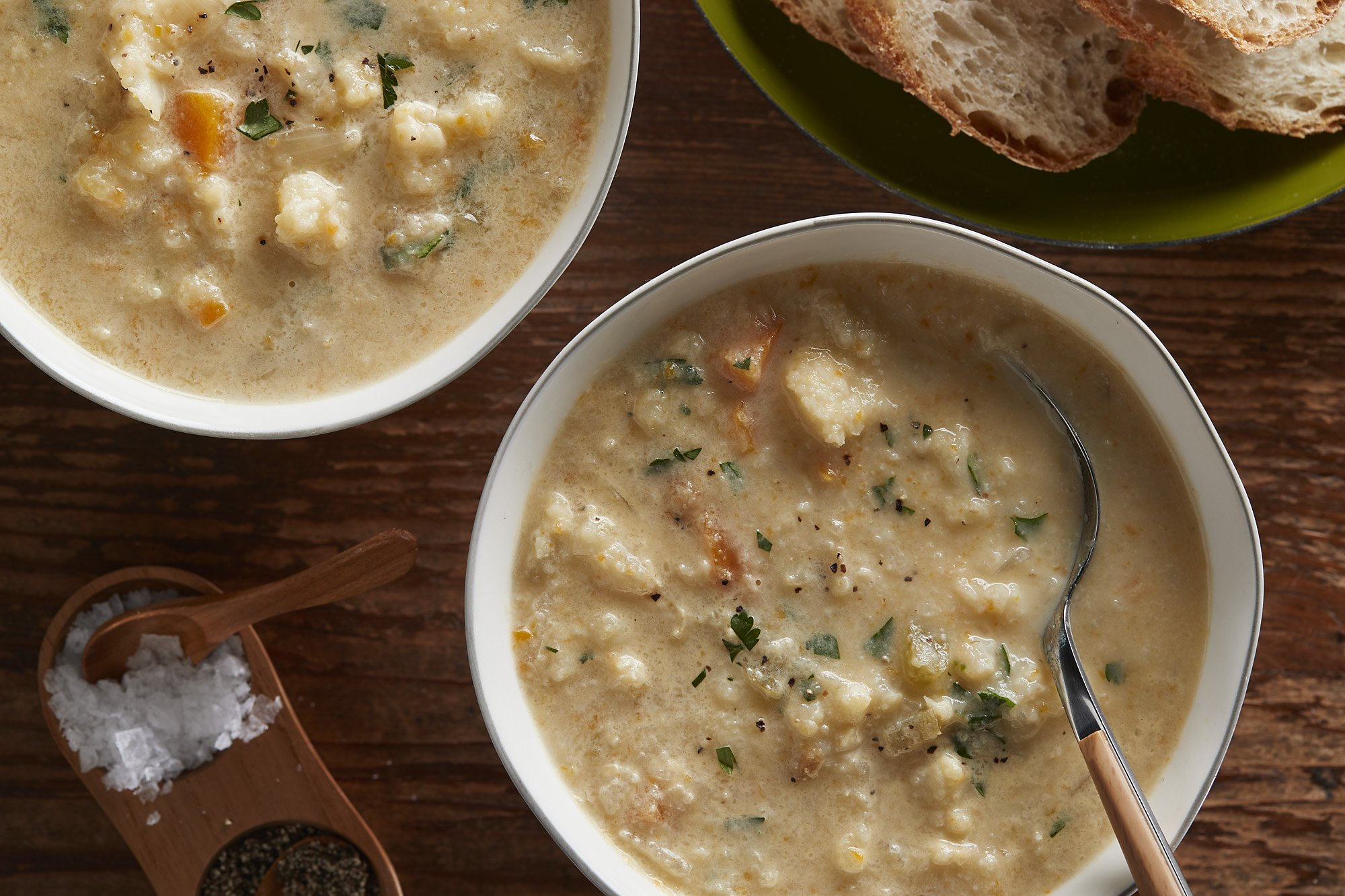 Bowls of cauliflower soup next to small containers of salt and pepper