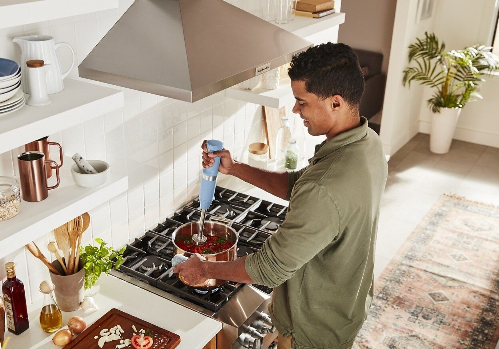 A man at the stovetop using a KitchenAid® hand blender to puree sauce.