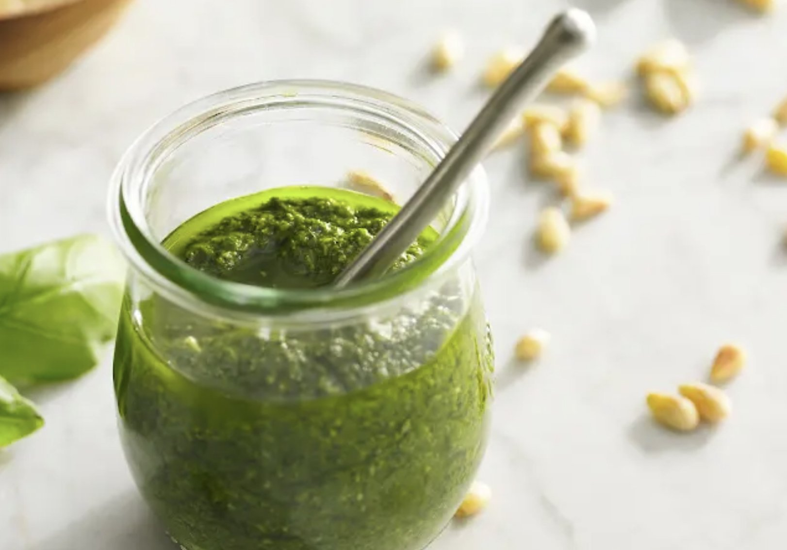 A glass jar filled with pesto