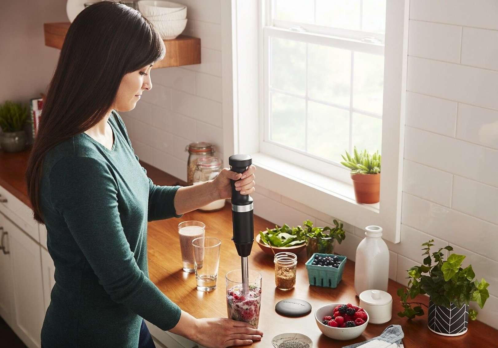 A woman making a smoothie with a KitchenAid® hand blender.