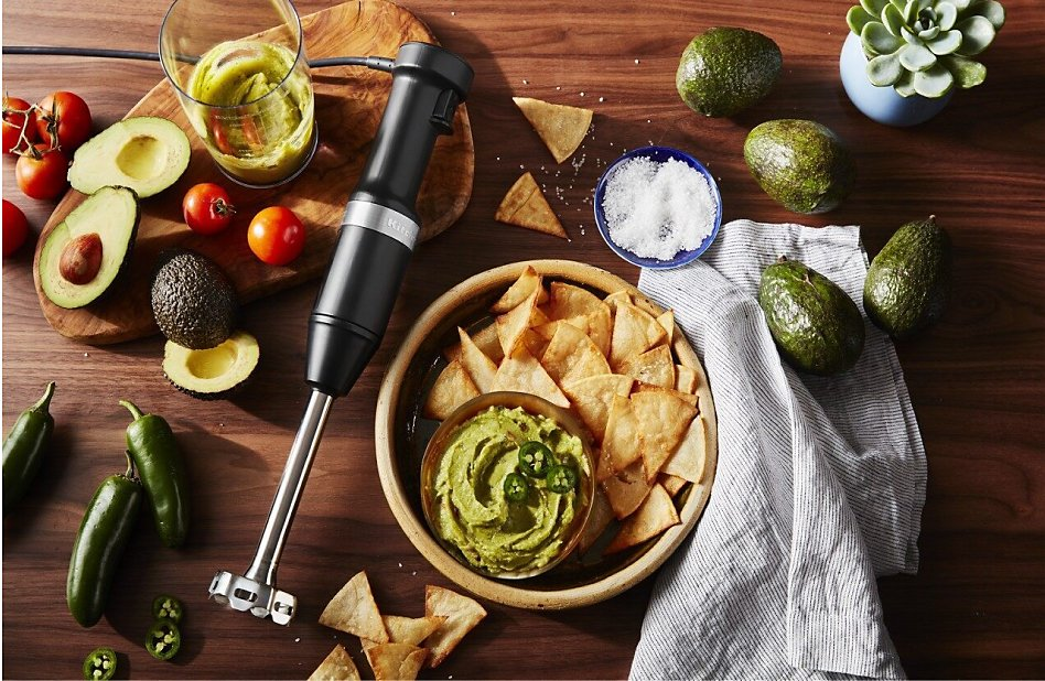 View of fresh produce and KitchenAid® hand blender next to bowl of guacamole