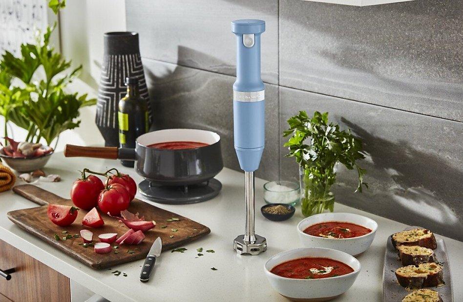 KitchenAid® hand blender in Blue Velvet next to pot of tomato sauce and fresh tomatoes