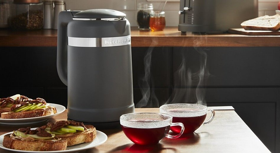 Electric tea kettle on a kitchen island next to cups of tea and breakfast plates.