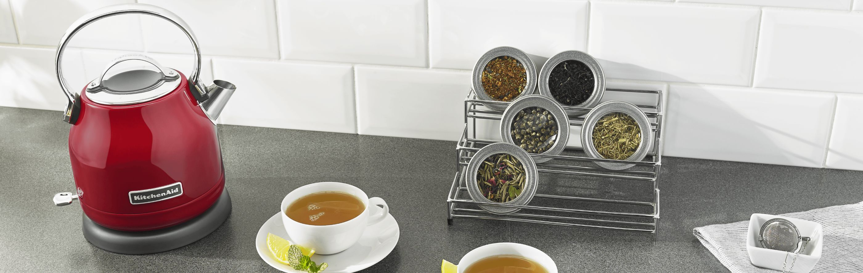 KitchenAid® electric tea kettle on countertop with cups of tea and containers of loose tea leaves.