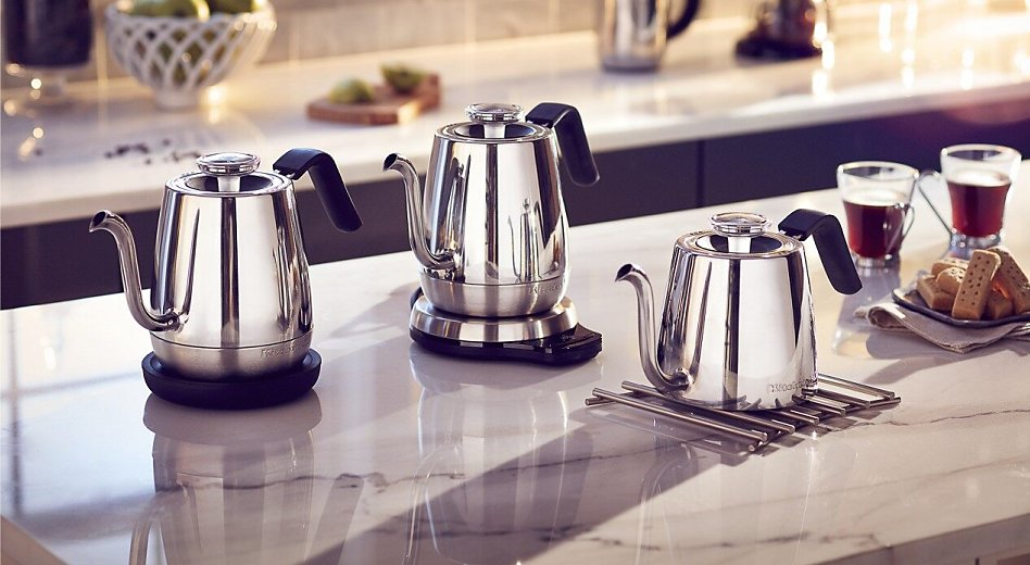 Three KitchenAid® electric tea kettles on the island next to cups of tea and cookie tray.