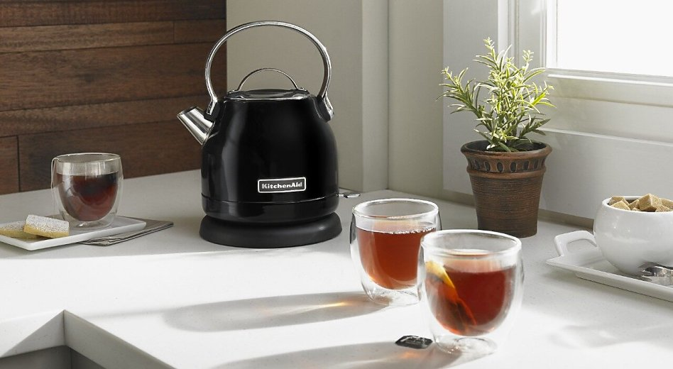 Black KitchenAid® 1.25 L Electric Kettle on a counter next to full cups of tea.