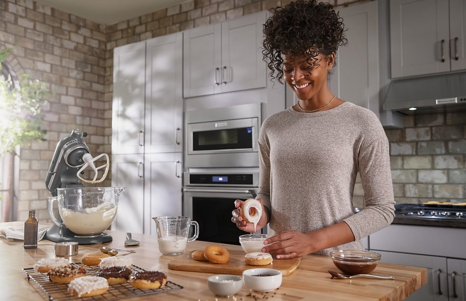 Smiling woman making donuts with a stand mixer in kitchen