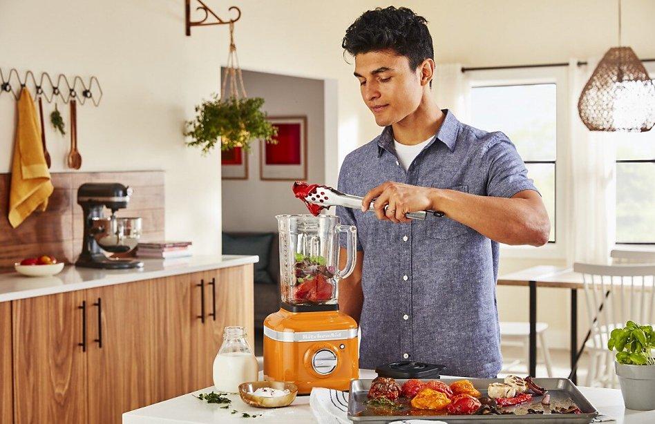 Smiling man putting roasted vegetables into a Honey colored blender