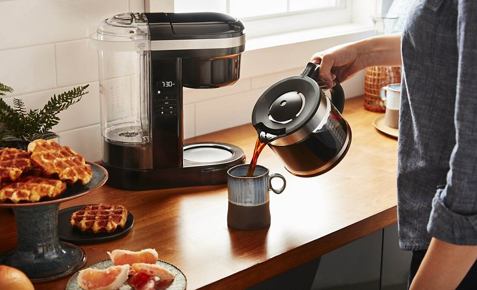 Woman pouring coffee into a mug with coffee maker in background