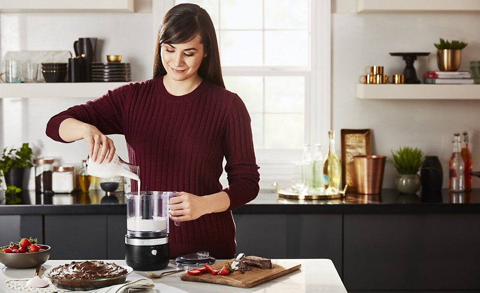 Smiling woman pouring cream into a cordless food chopper