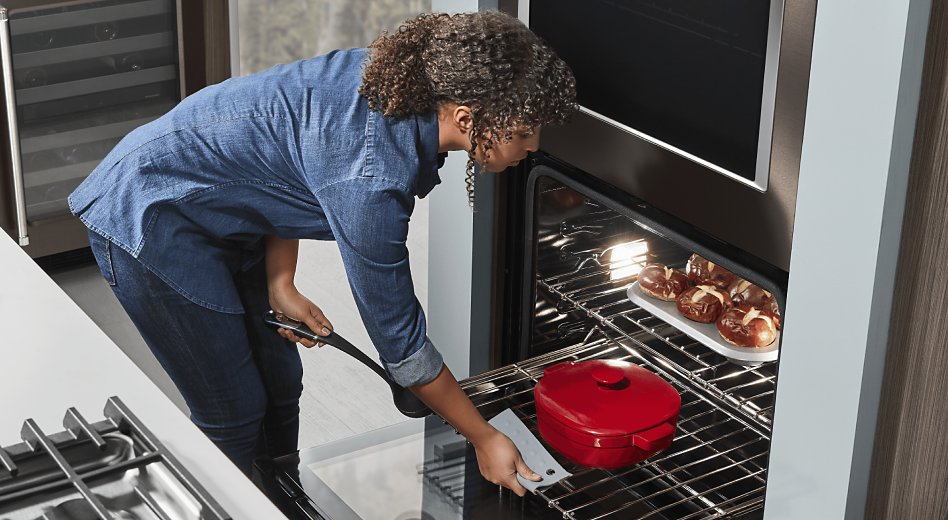 Woman placing red dutch oven in oven with homemade pretzel rolls baking on upper rack