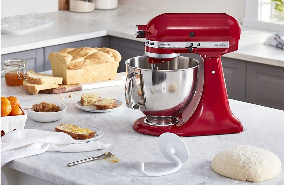 Red stand mixer on counter with bread dough and baked loaf