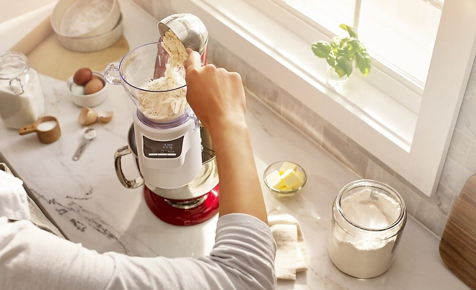 Woman pouring flour in the sifter + scale attachment for stand mixer