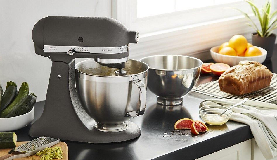 Grey stand mixer on counter with two stainless steel bowls and quick bread