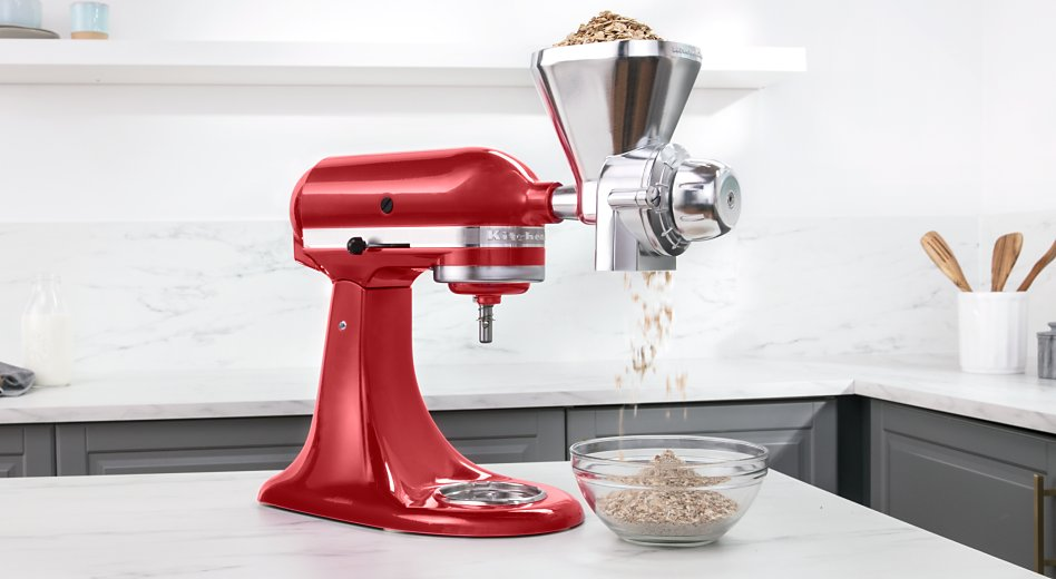 A KitchenAid® stand mixer fitted with an All Metal Grain Mill attachment