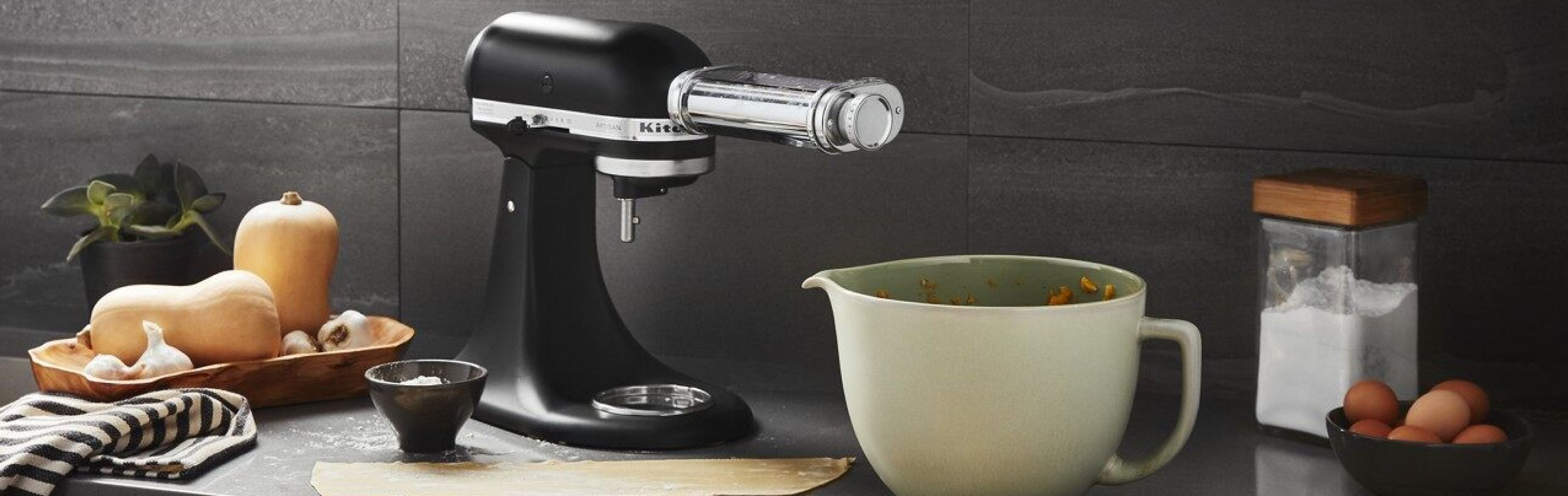 Black stand mixer with pasta attachment next to sage green mixing bowl and butternut squash