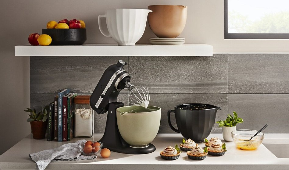 Black stand mixer on counter with various bowls and tartlette desserts
