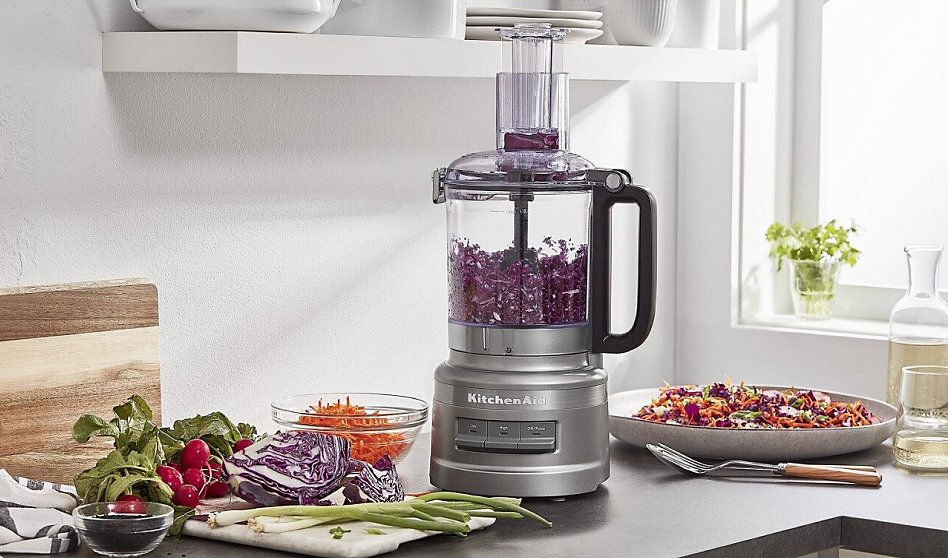 Silver food processor shredding red cabbage on counter