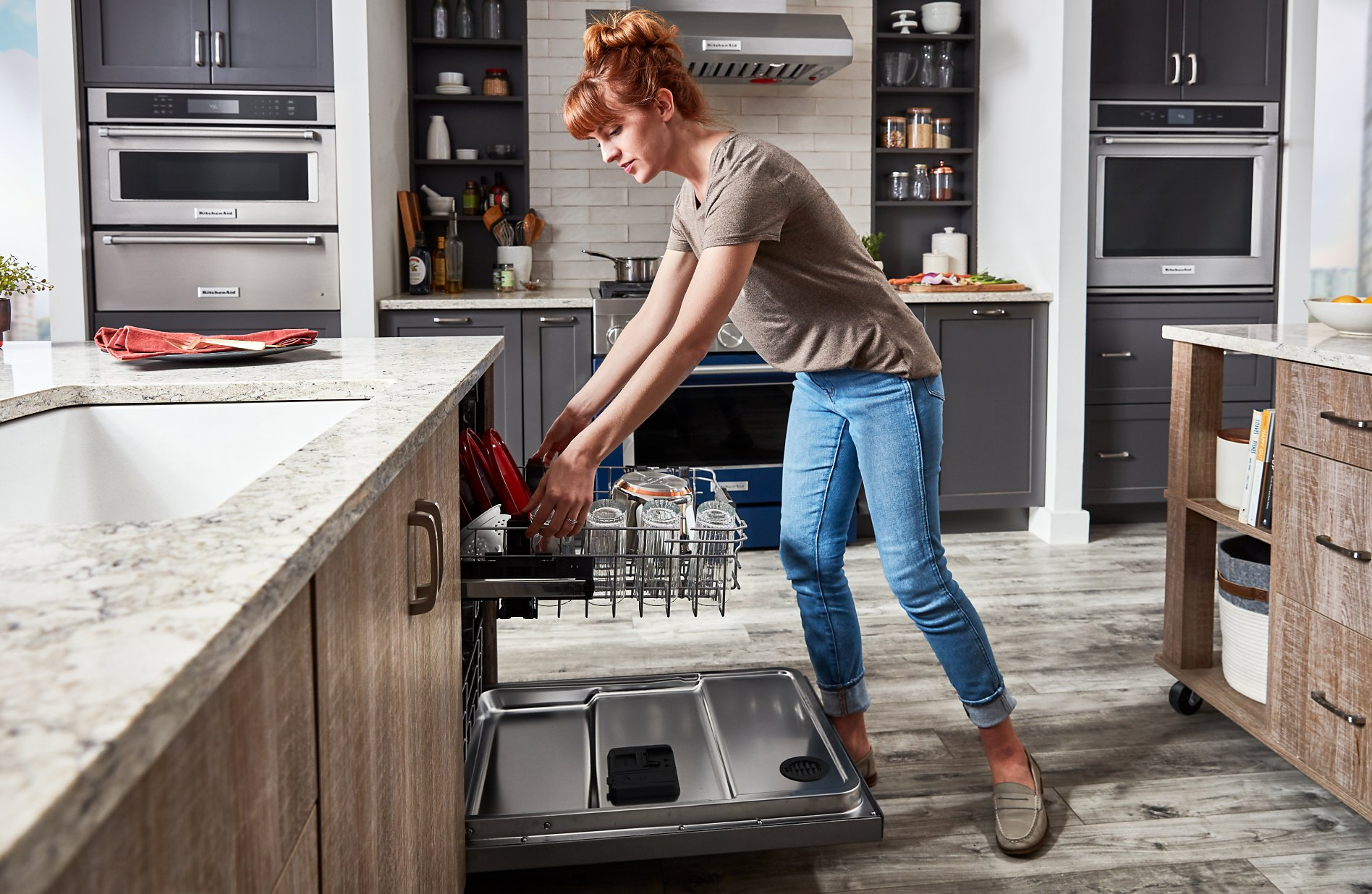 Woman rolling out the top rack of a dishwasher in a large kitchen