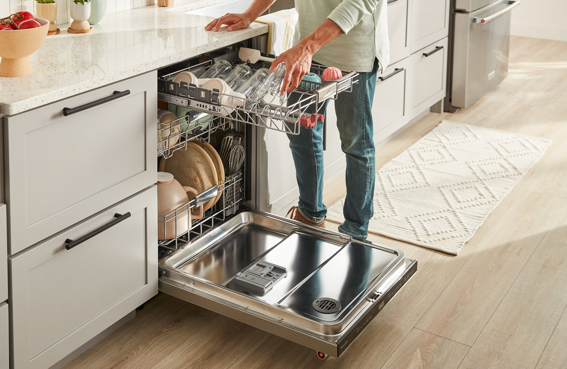 Person placing a full-sized glass in a third rack dishwasher